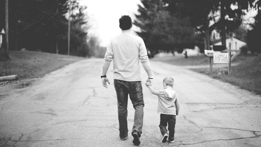 Father and son walking down a road